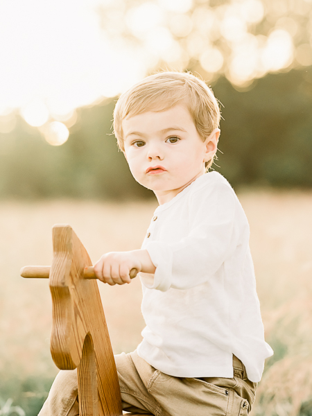Little toddler boy sitting on wood rocking horse during photography session in Katy area field