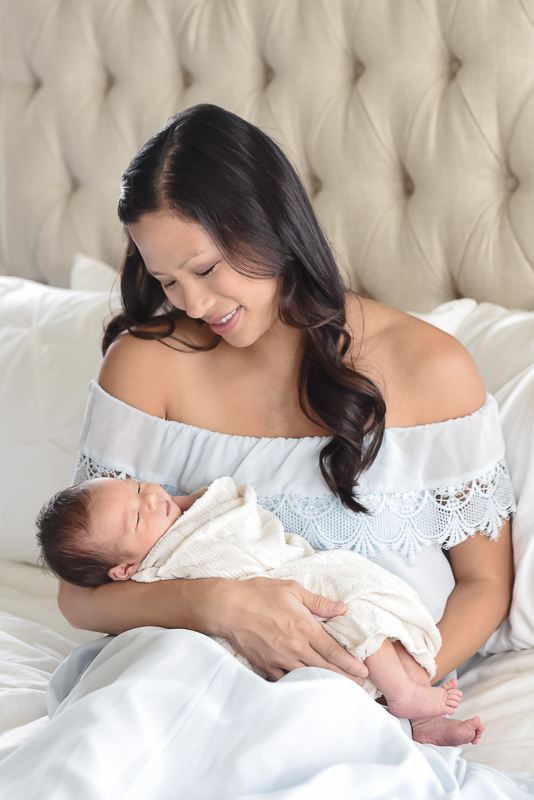 mom on bed holding newborn baby during in home newborn photography session.