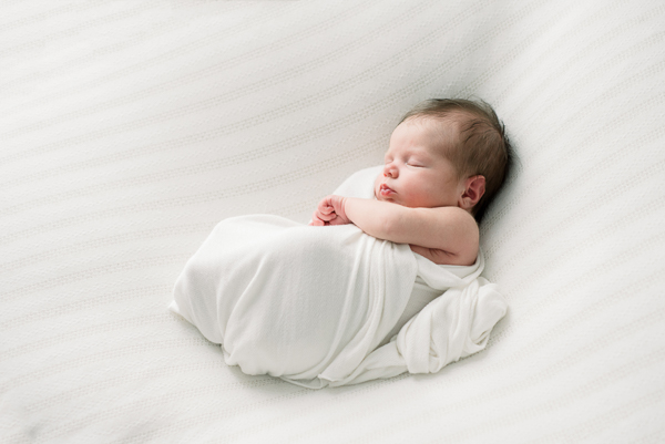 newborn on white blanket unposed