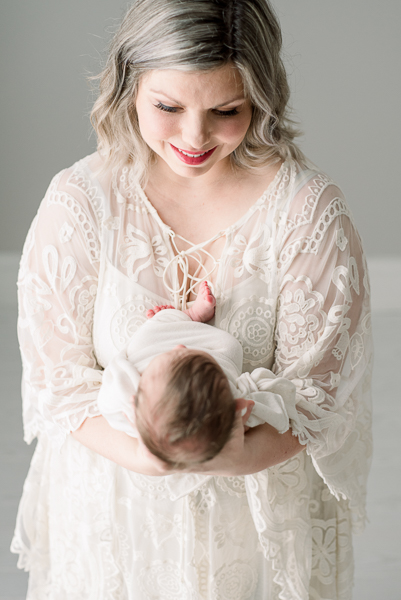 mom holding newborn baby during newborn photo session