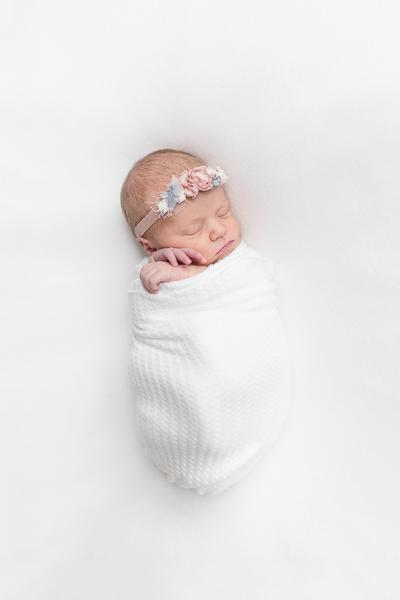 newborn baby on white blanket