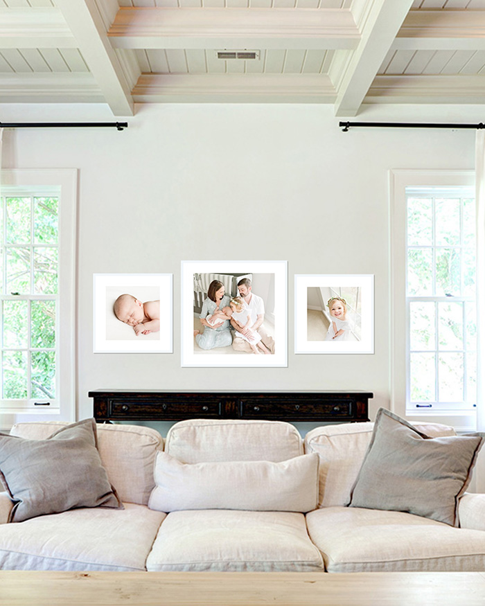 three newborn and baby photos in three white frames on living room wall